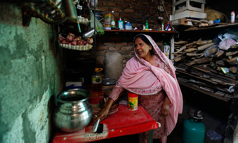 A Christian woman works in her kitchen during a power cut at her home in Islamabad. Power can be out for up to 20 hours a day in the summer.