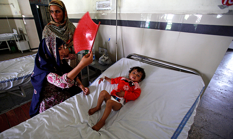 Shahla Ashiq uses a hand fan to cool off her daughter, Momina, 2, during a power outage at a hospital in Gujar Khan.