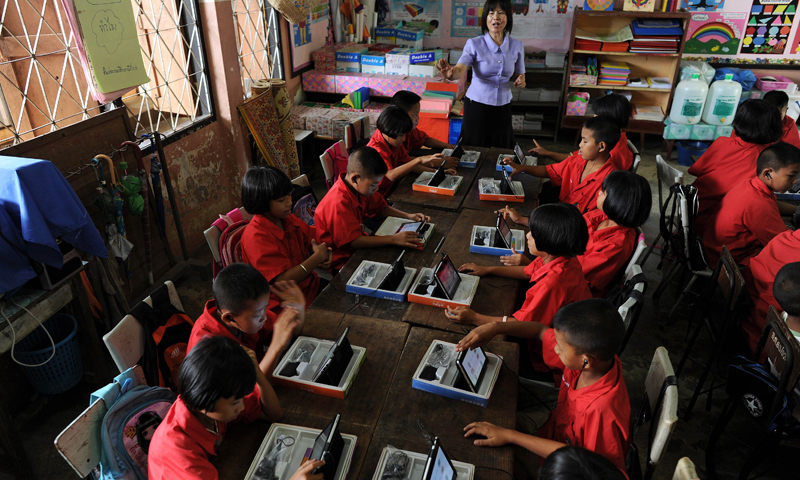 This picture taken on May 27, 2013 shows students using tablets during a lesson at a classroom in the Ban San Kong school of Mae Chan, a town located in Thailand