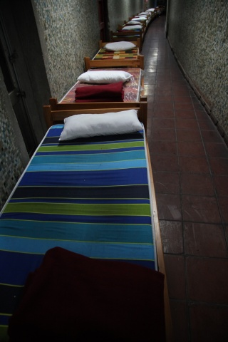 Beds line a hallway in the indoor stadium Estadio Victor Jara.