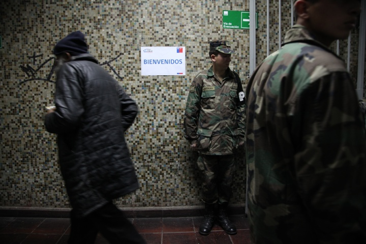 Soldiers guard the entrance of a homeless shelter at the indoor stadium Estadio Victor Jara.