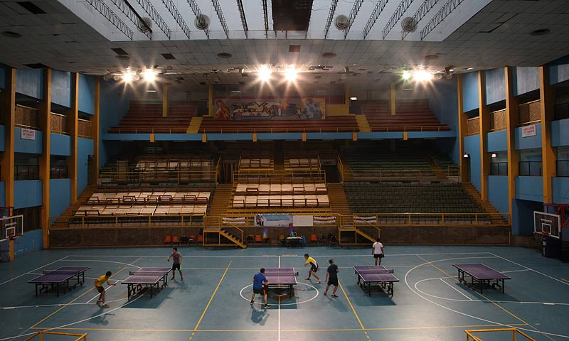 Students play ping-pong at the indoor stadium Estadio Victor Jara.