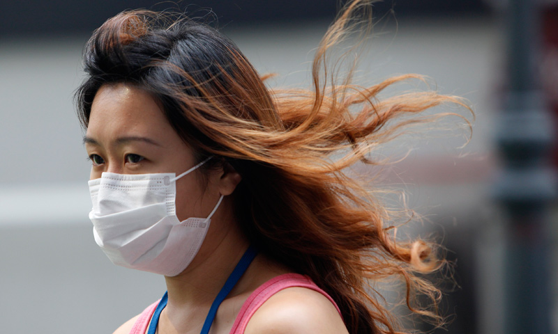 A woman wearing a face mask walks in the hazy central business district of Singapore. — Reuters Photo