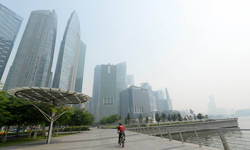 "A cyclist rides along the pier in front of buildings blanketed by haze in Singapore. Singapore's Pollutant Standards Index again shot above the ""unhealthy"" threshold of 152.  — AFP Photo"