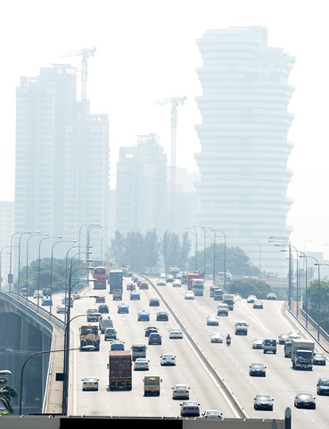 A view of the highway leading out of the central business district as buildings are blanketed with haze. — AFP Photo