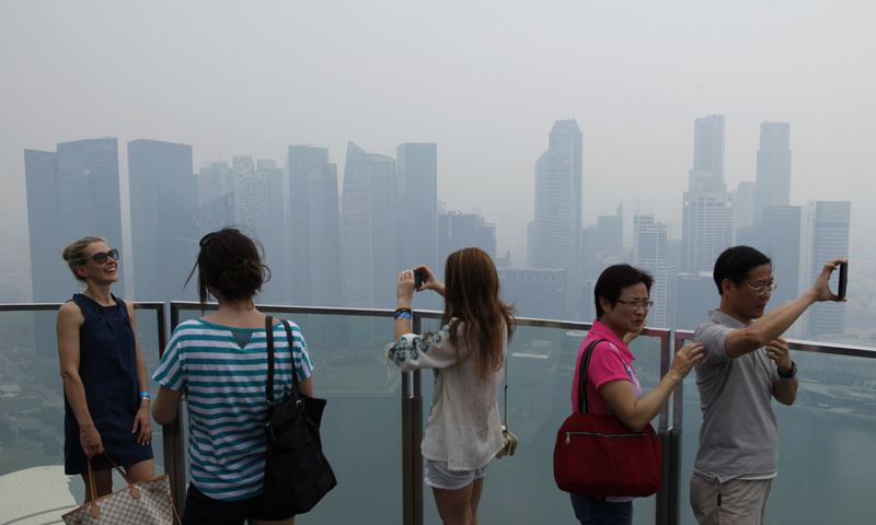 Visitors take photos at an observation deck of Marina Bay Sands Skypark overlooking the haze covered skyline of Singapore. — Reuters Photo