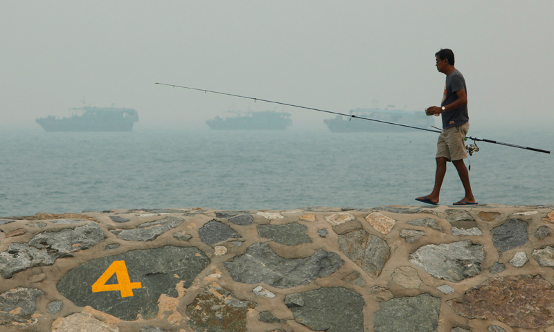 A man fishes on a breakwater along East Coast Park on a hazy day in Singapore June 17, 2013. — Reuters Photo