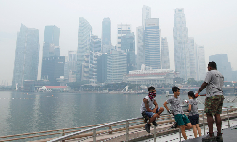 Workers take a break in front of the hazy skyline of Singapore June 17, 2013. — Reuters Photo