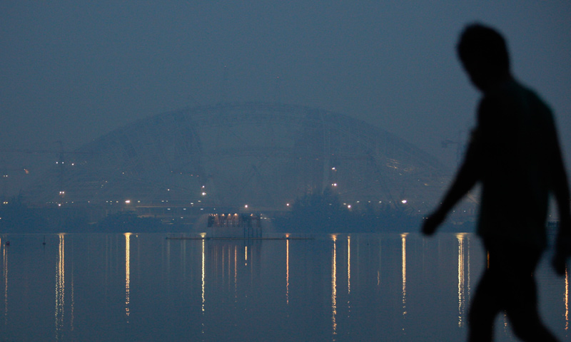 A man walks past the new National Stadium under construction on a hazy evening in Singapore June 17, 2013. — Reuters Photo