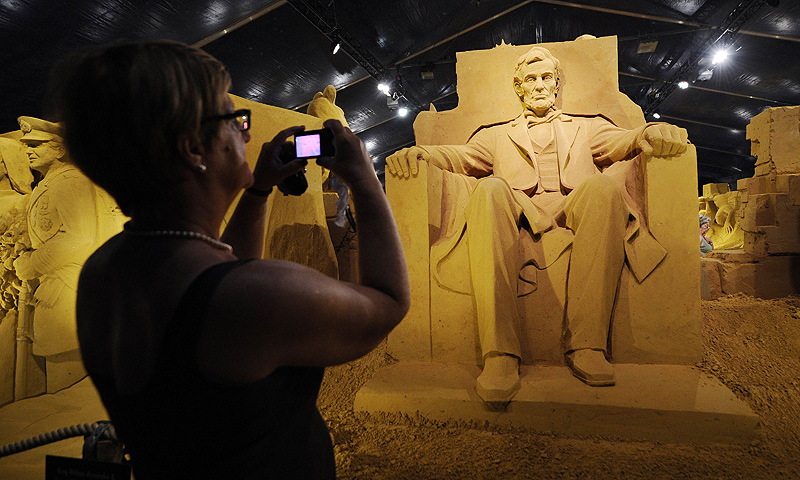 A person takes pictures of a sand sculpture representing the Lincoln Memorial during the Sand Sculpture Festival in Blankenberg on June 18, 2013. — AFP Photo