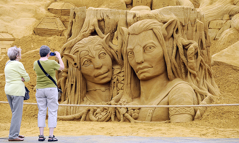 People take pictures of a sand sculpture representing Avatar science fiction movie's characters during the Sand Sculpture Festival in Blankenberg on June 18, 2013. — AFP Photo