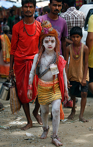 A young Indian child, dressed like Lord Shiva, stands among devotees at the Kamakhya temple in Gauhati, India, Wednesday, June 19, 2013. — AP Photo