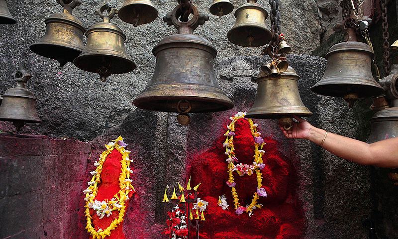 An Indian woman rings bells at the Kamakhya temple in Gauhati, India, Wednesday, June 19, 2013. — AP Photo