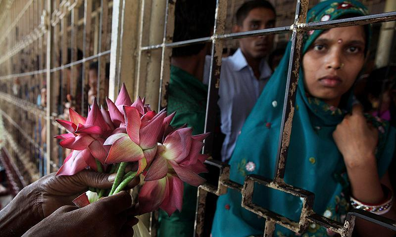 An Indian man sells lotus flowers to devotees standing behind a fence at the Kamakhya temple in Gauhati, India, Wednesday, June 19, 2013. — AP Photo