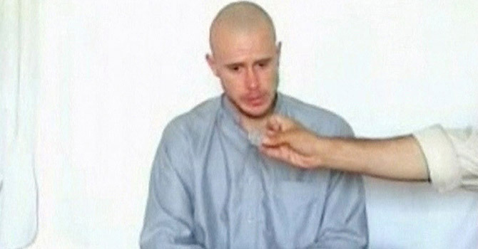 US Army Private Bowe Bergdahl watches as one of his captors displays his identity tag to the camera at an unknown location in Afghanistan, in this still image taken from video on July 19, 2009. — Photo by Reuters