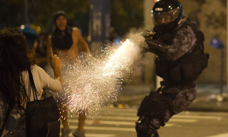 A military police from the special unit Chope shoots with a tear gas gun late on June 19, 2013 to disperse protestors during clashes in the center of Niteroi, 10 kms from Rio de Janeiro. Protesters battled police late on June 19, even after Brazil's two biggest cities rolled back the transit fare hikes that triggered two weeks of nationwide protests.  The fare rollback in Sao Paulo and Rio de Janeiro marked a major victory for the protests, which are the biggest Brazil has seen in two decades. – Photo by AFP