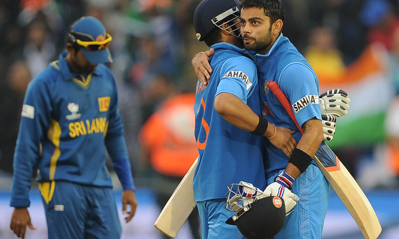 India's Virat Kohli (R) and Suresh Raina (C) embrace after securing victory in the 2013 ICC Champions Trophy semi-final cricket match between India and Sri Lanka at the Cardiff Wales Stadium in Cardiff, south Wales on 20, June 2013. – Photo by AFP