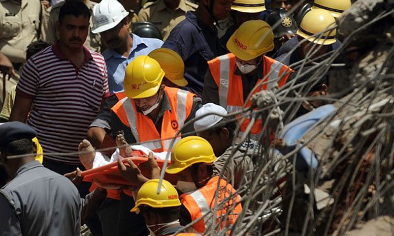 Indian rescue workers carry a dead body from the site of a building collapse in thane, on the outskirts of Mumbai on April 5, 2013. — File Photo by AFP