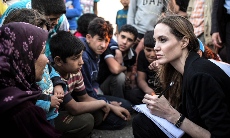 A handout picture made available by the United Nations High Commission for Refugees (UNHCR) shows US actress Angelina Jolie (R) listening to Syrian refugees in a Jordanian military camp based the the Jordan-Syria border on June 18, 2013. — AFP Photo