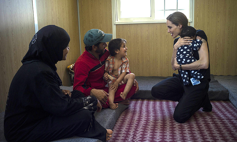 A handout picture made available by the United Nations High Commission for Refugees (UNHCR) shows US actress Angelina Jolie (R) holding a baby as she visits a family of syrian refugees in their apartment in Amman on June 19, 2013. — AFP Photo
