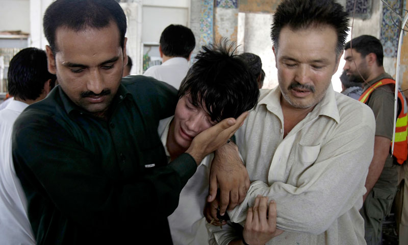People comfort a boy who lost his family member in the suicide bombing at a Madrassa Hussainia mosque in Peshawar on Friday, June 21, 2013. —AP Photo