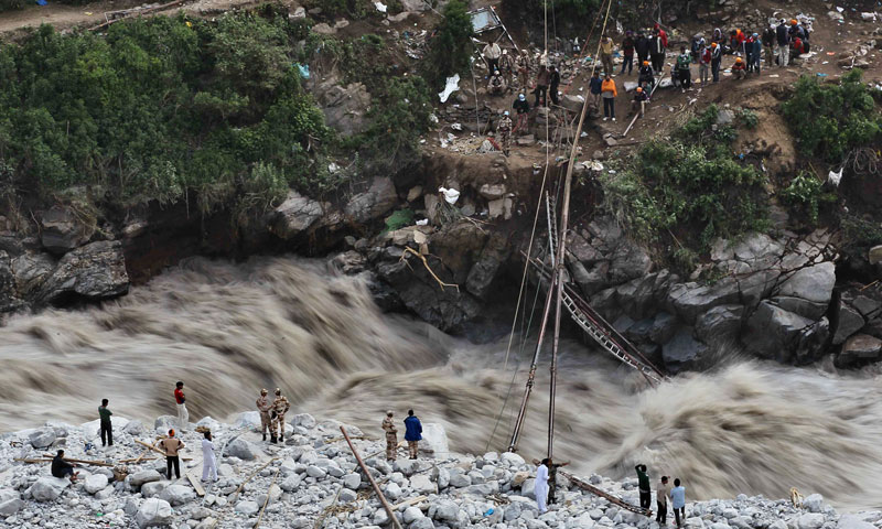 Water gushes down a river as Indian paramilitary soldiers stand near a temporary bridge after it was damaged as stranded pilgrims wait to be evacuated on the other side in Govindghat, India, Saturday, June 22, 2013. —AP Photo