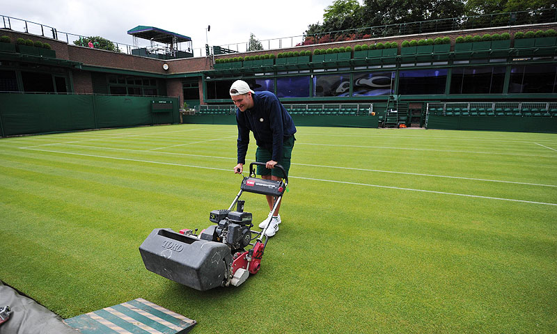 A ground staff mows the grass on a court at the All England Tennis Club in Wimbledon. -Photo by AFP