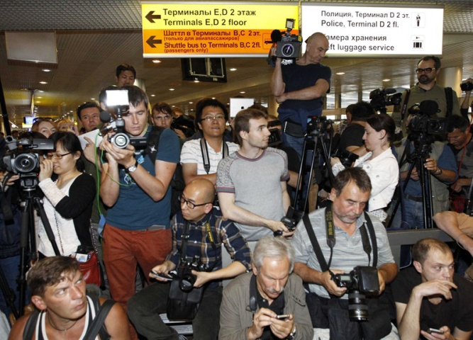 Journalists await passengers of a flight from Hong Kong while trying to ascertain whether fugitive former US spy agency contractor Edward Snowden was aboard, at Moscow