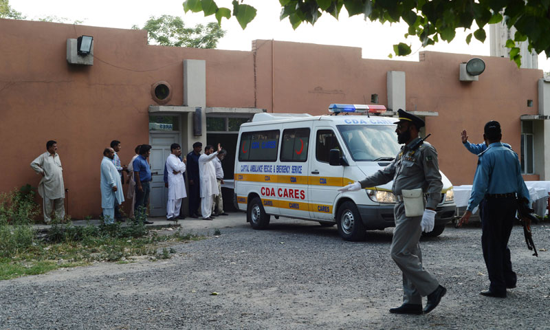 Pakistani security personnel and rescuers gather around ambulance moving coffins with foreign tourists at a hospital in Islamabad on June 23, 2013. - Photo by AFP