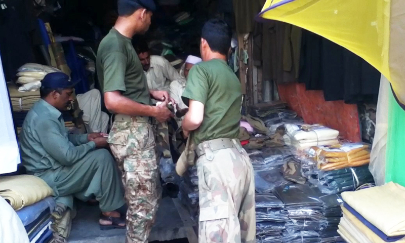 The uniform of the Pakistan Army and other military accessories can also be found hanging outside the shops in the market. Army personnel and civilians buy this gear from this market, although it is banned by local administration. — Screen grab from video provided by author.