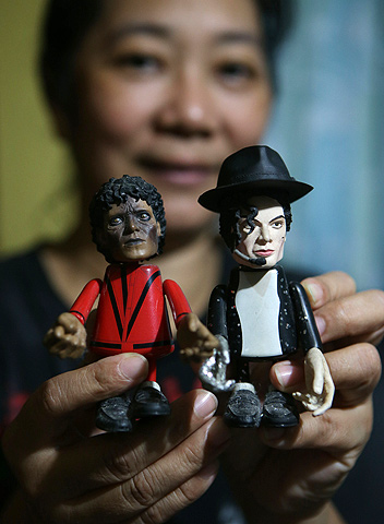Filipino fan Elizana Mamucud shows Michael Jackson dolls at her house in Manila, Philippines on Tuesday June 25, 2013. — AP Photo