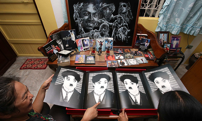 Fans of Michael Jackson, Elizana Mamucud, left, and Teresita Cailo show images of Jacskon dressed at  silent movie legend Charlie Chaplin  along with  other assorted memorabilia in Manila. — AP Photo