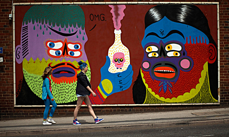 "Two girls walk past a mural painted on a wall in Blackpool, northern England June 18, 2013. The mural is part of the ""Sand, Sea and Spray"" outdoor art festival, which has seen 40 urban artists from around the world paint murals on buildings across the town centre. — Reuters Photo"