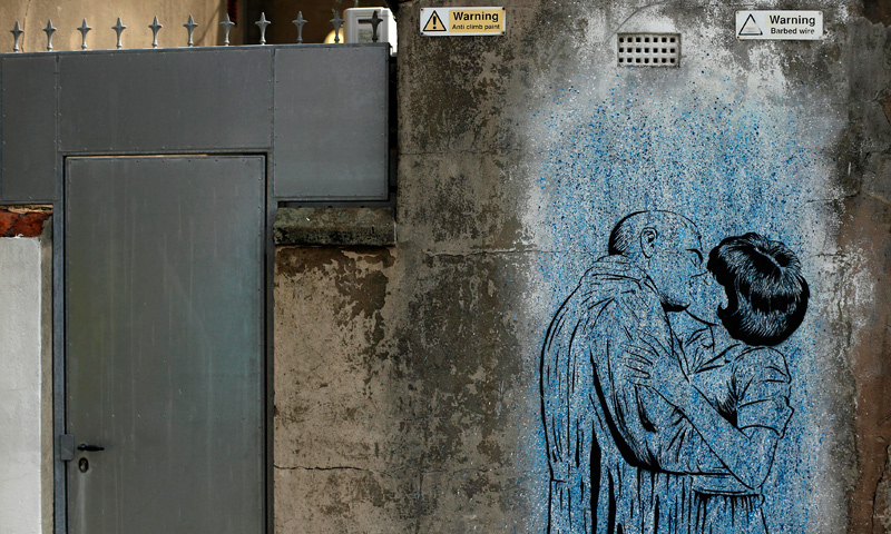 "A man walks past murals painted on the wall of a car park in Blackpool, northern England June 18, 2013. The mural is part of the ""Sand, Sea and Spray"" outdoor art festival, which has seen 40 urban artists from around the world paint murals on buildings across the town centre. — Reuters Photo"