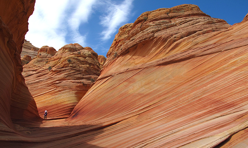 A hiker on a rock formation known as The Wave  in the Vermilion Cliffs National Monument in Arizona.