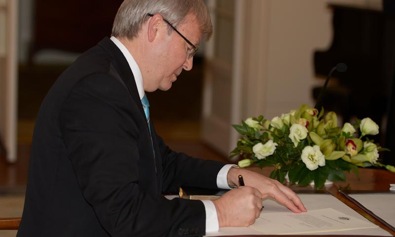 Kevin Rudd signs a document as he is sworn in as Australia's new prime minister at Government House in Canberra on June 27, 2013. .— Photo by AFP