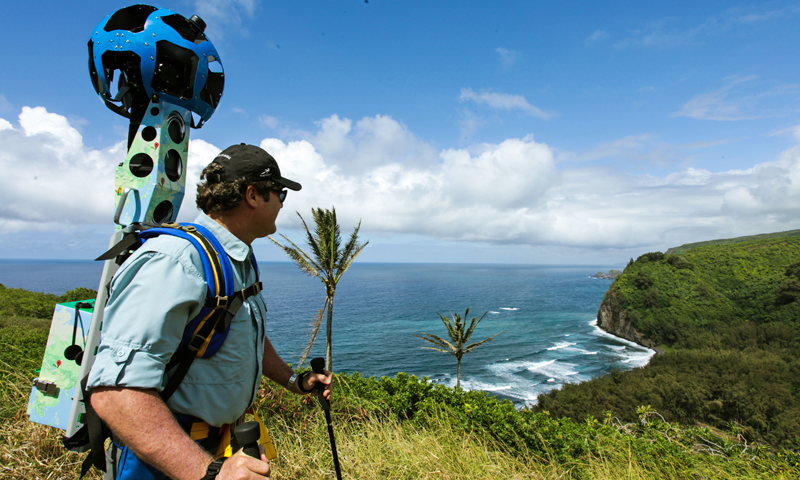 In this undated photo provided by Google, Rob Pacheco, president of Hawaii Forest & Trail, takes in the view at Pololu Valley's Awini Trail near Kapaau, Hawaii, while wearing the Street View Trekker. Hawaii's volcanoes, rainforests and beaches will soon be visible on Google Street View. The Mountain View, Calif., company said Thursday June 27, 2013  it was lending its backpack cameras to a Hawaii trail guide company to capture panoramic images of Big Island hiking trails. — AP Photo