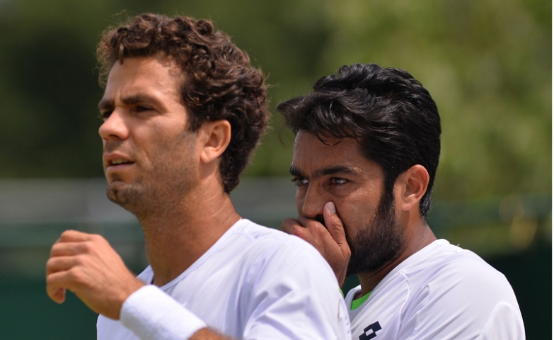 Pakistan's Aisam Qureshi (R) and his partner Netherlands' Jean-Julien Rojer (L) talk as they play against Germany's Dustin Brown and Australia's Rameez Junaid during their first round men's doubles match on day four of the 2013 Wimbledon  Tennis Championships.