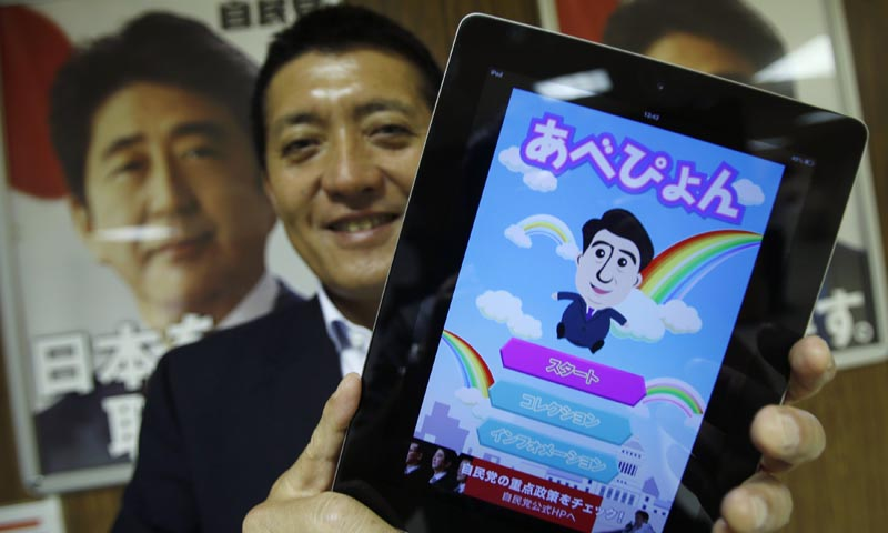 "Takuya Hirai, Director of Internet Media Division of Japan's ruling Liberal Democratic Party (LDP), poses with an iPad displaying ""Abe Pyon"", LDP's official game application programme featuring Shinzo Abe, Japan's Prime minister and LDP's leader, at the LDP headquarters in Tokyo June 27, 2013. — Reuters Photo"