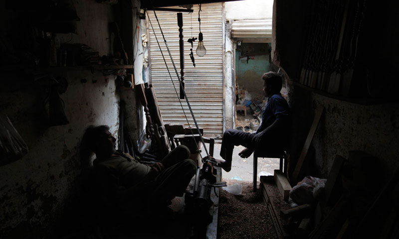Carpenters at a workshop pause during a power outage in a Karachi June 15, 2013. — Photo by Reuters