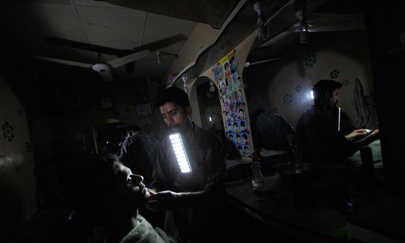 A barber (R) holds a portable emergency light in his mouth while shaving a customer during a power outage at a low income neighborhood in Karachi June 29, 2013. — Photo by Reuters