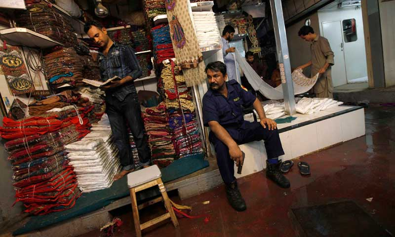 A private armed security guard keeps his eyes on a passage as shopkeepers work along a covered cloth market in Karachi, June 13, 2013. — Photo by Reuters