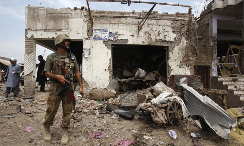 This Sunday, June 30, 2013 photo shows a army standing alert at the site of car bombing that killed more  than a dozen people and left many injured in Peshawar, Pakistan. There is concern that the country's leaders lack a coherent strategy to fight the pervasive problem of violent extremism. — AP Photo.