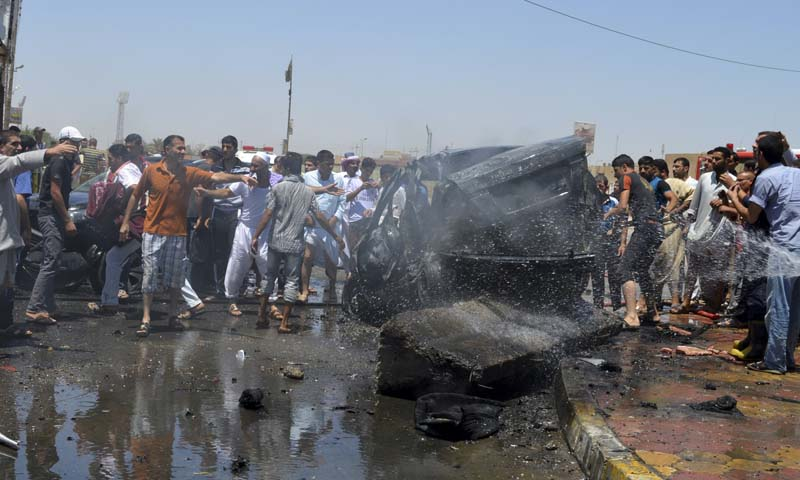 People gather at the site of a suicide car bomb attack in the city of Samarra, some 100 km (62 miles) north of Baghdad July 5, 2013. — Photo by Reuters