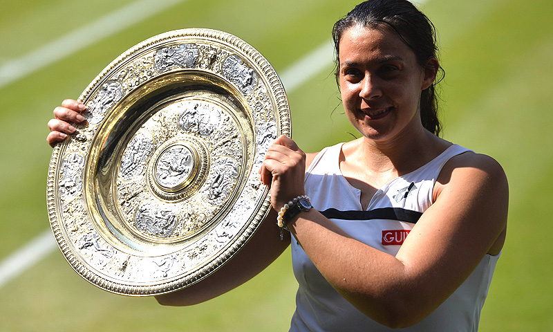 France's Marion Bartoli poses with the trophy after beating Germany's Sabine Lisicki in their women's singles final. -Photo by AFP