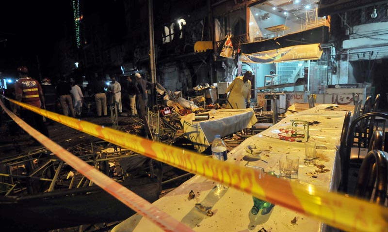 Pakistani police officials check the site of bomb explosion on a food park in Lahore on July 6, 2013. A bomb explosion on July 6 in a bustling food park in Pakistan's eastern city of Lahore killed at least three people and wounded 38 others. — Photo by AFP