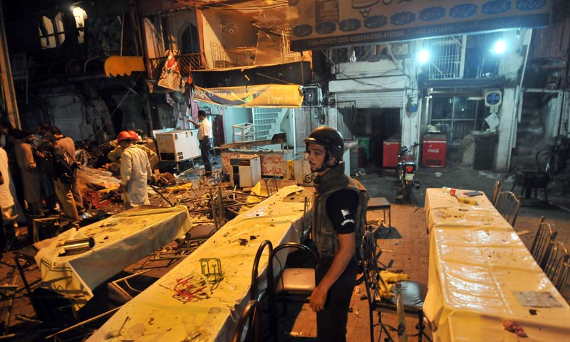Pakistani police officials check the site of bomb explosion on a food park in Lahore on July 6. — Photo by AFP