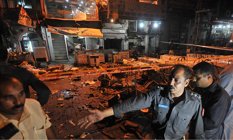 Pakistani police officials check the site of bomb explosion on a food park in Lahore on July 6, 2013. — Photo by AFP
