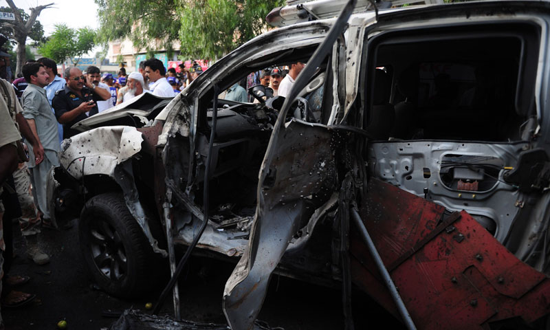 Security officials inspect the wreckage of the vehicle at the site of the bomb blast in Karachi on July 10, 2013.—AFP Photo
