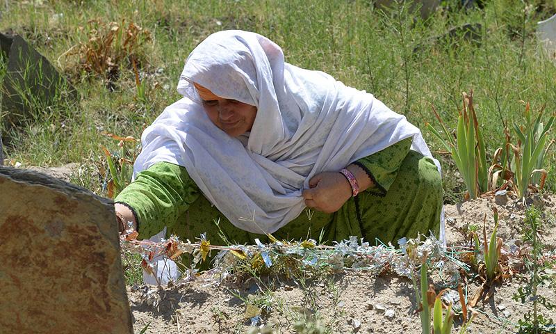Jan Bano sits at her daughter's grave at Akhun Baba. -Photo by AFP